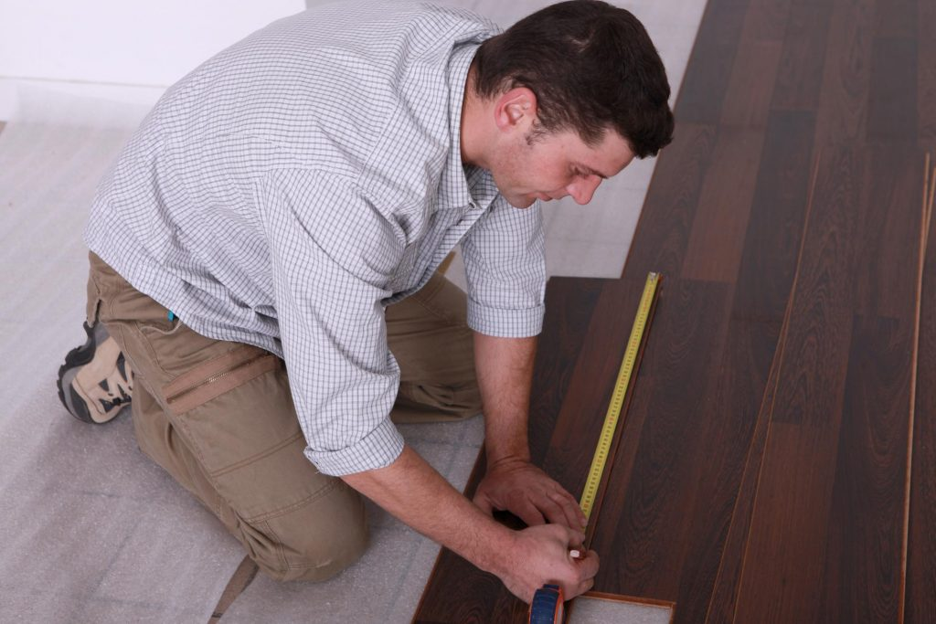 man measuring the wood floor